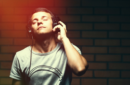 grunge music background: Portrait of a handsome young man listening to music