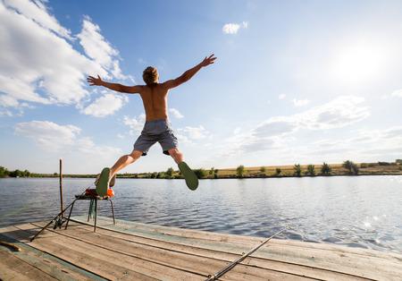 pecheur: Heureux homme sautant sur la jetée avec lac et le ciel en arrière-plan