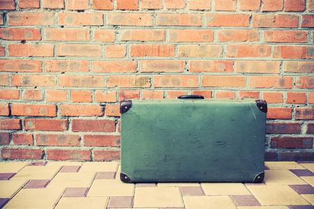 maleta: Maleta de la vendimia en la calle y ladrillos fondo Foto de archivo