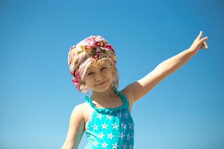 mignonne petite fille: Cute petite fille en maillot de bain contre le ciel bleu, portrait en plein air