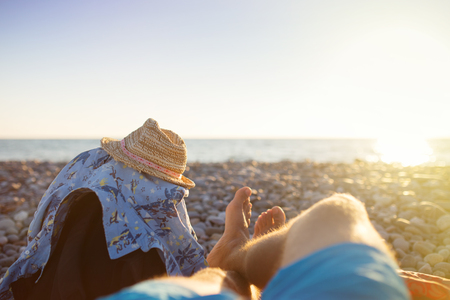 mochila viaje: Perspectiva en primera persona de las piernas del hombre en la playa de la puesta del sol. Concepto del recorrido