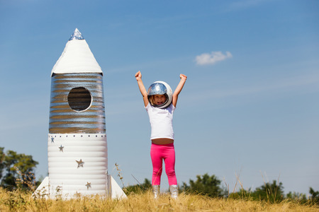Happy child dressed in an astronaut costume playing with hand made rocket. Summer outdoor 免版税图像