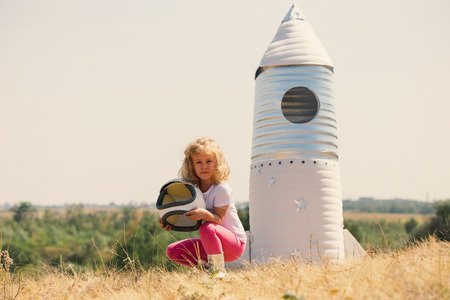 astronauta: Happy child dressed in an astronaut costume playing with hand made rocket. Summer outdoor. Retro tinted