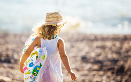 only one girl: Adorable little girl with inflatable air mattress on beach Stock Photo