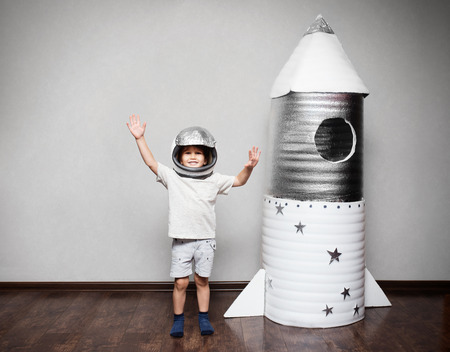 Happy child dressed in an astronaut costume playing with hand made rocket.