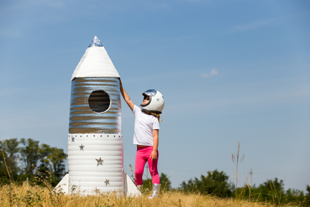 child rocket: Happy child dressed in an astronaut costume playing with hand made rocket. Summer outdoor Stock Photo