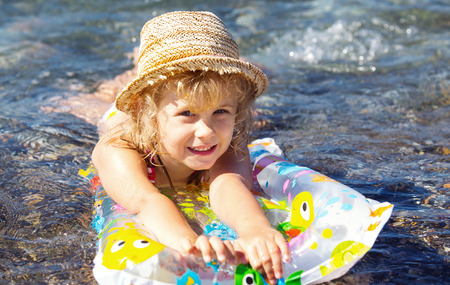 only one girl: Adorable little girl on air inflatable mattress in the sea