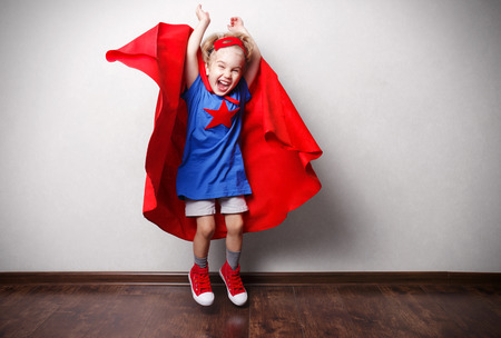 Happy child in superhero suit against gray wall.