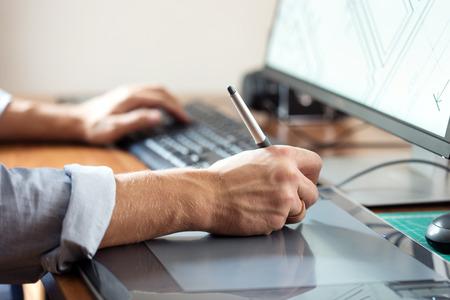 trabajadores: Dise�ador gr�fico que usa la tableta digital y el ordenador en la oficina o en el hogar