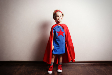 courageous: Happy child in superhero suit against gray wall.