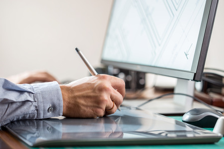 graphics tablet: Graphic artist using graphics tablet at his desk