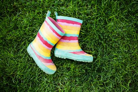 rain boots: botas de lluvia de rayas en la hierba verde Foto de archivo