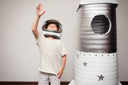 child rocket: Happy child dressed in an astronaut costume playing with hand made rocket.