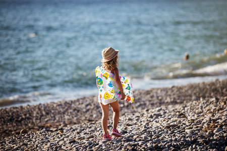 Adorable little girl with inflatable air mattress on beach Stock Photo