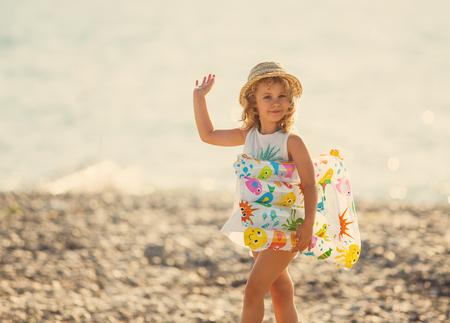 beauty girls: Cute little girl in swimwear waving hand standing on beach, outdoor portrait Stock Photo