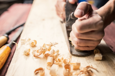 scobs: Man working with hand jack plane, close up photo Stock Photo