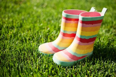 rain boots: Striped rain boots on green grass