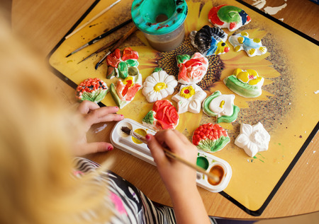 children hands: Child painting a ceramic pottery model