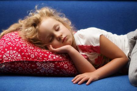 asleep: Little girl sleeps on a sofa, close up photo Stock Photo