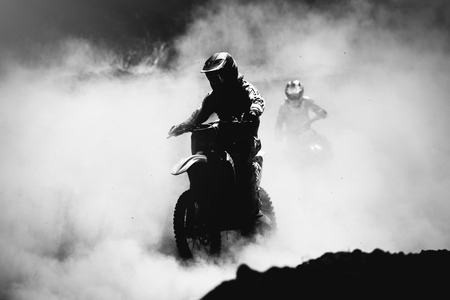 action: Motocross racer accelerating in dust track, Black and white, high contrast photo