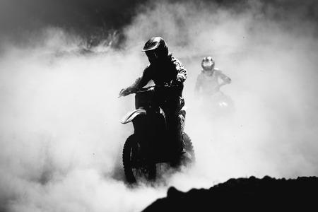 acion: Piloto de motocross en la pista de aceleración polvo, Negro y blanco, foto de alto contraste