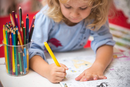 preschooler: Portrait of child girl drawing with colorful pencils