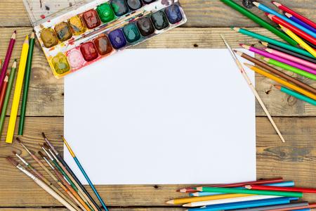 paleta de pintor: paleta de pintura plástica con pintura y pinceles en la mesa de madera Foto de archivo