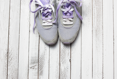 athletic wear: Pair of sport shoes on white wooden background