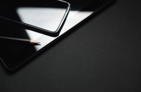 electronic tablet: Smartphone Leaning On Tablet close up photo. Electronic devices on black background. Stock Photo