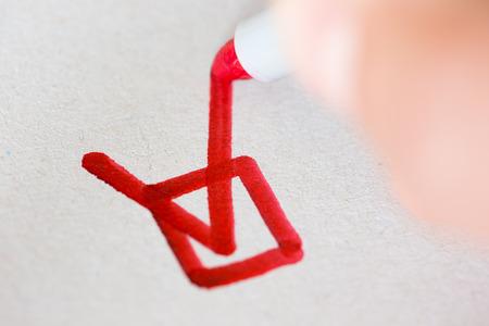 marker: La mano con lápiz rojo marcando una casilla de verificación Foto de archivo