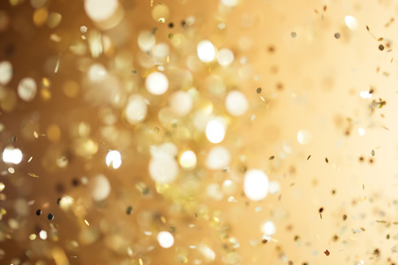 glowing: Christmas gold background. Golden holiday glowing abstract glitter defocused background