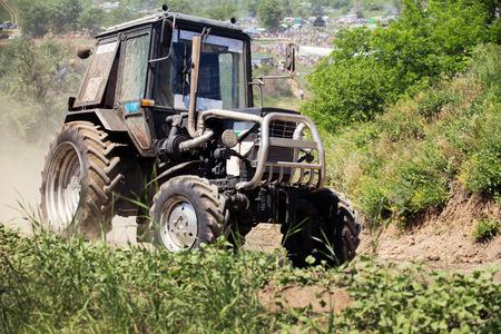 harrowing: Farm tractor goes on road Stock Photo