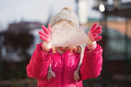 pellucid: Portrait happy girl with piece of ice in hand Stock Photo