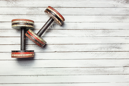 Two old dumbbells on white wooden background. Archivio Fotografico