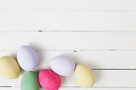white eggs: Easter eggs painted in pastel colors on white wooden background Stock Photo