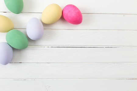 vibrant background: Easter eggs painted in pastel colors on white wooden background Stock Photo