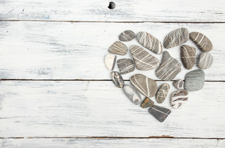 wood panel: A heart shaped pebble stones on a old wood planks