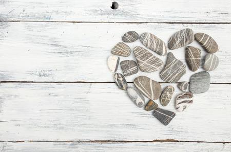 Een hartvormige kiezelstenen op een oude houten planken