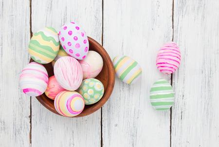 decoracion mesas: Huevos de Pascua pintados en colores pastel sobre fondo blanco de madera. concepto de Pascua Foto de archivo
