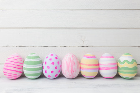 Easter eggs painted in pastel colors on white wooden background. Easter concept Foto de archivo