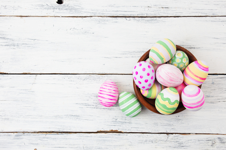 Easter eggs painted in pastel colors on white wooden background. Easter concept Archivio Fotografico