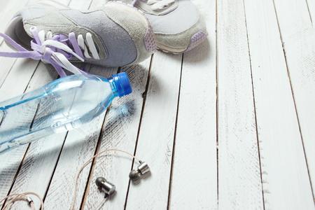 deporte: Par de zapatos de deporte, botella de agua y auriculares en el fondo de madera blanca