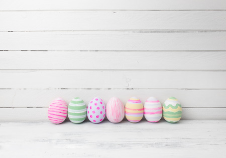Easter eggs painted in pastel colors on white wooden background. Easter concept Standard-Bild