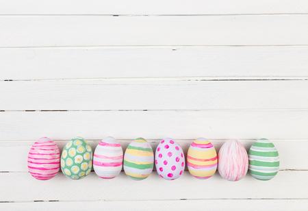 Easter eggs painted in pastel colors on a white wood background Standard-Bild