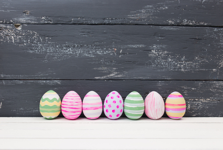 Easter eggs painted in pastel colors on a white wood background 写真素材
