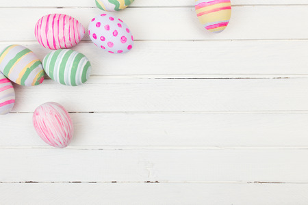 Easter eggs painted in pastel colors on a white wood background Foto de archivo