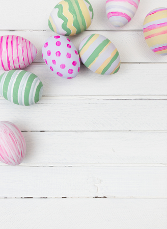 easter decorations: Easter eggs painted in pastel colors on a white wood background Stock Photo