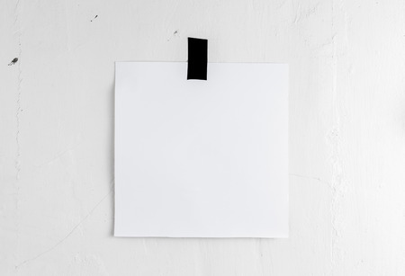 white poster: Blank white poster hanging on a tape on the wall. Template background for your design.