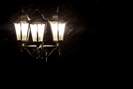 old style: Street lamps in snowfall close up photo. Stock Photo