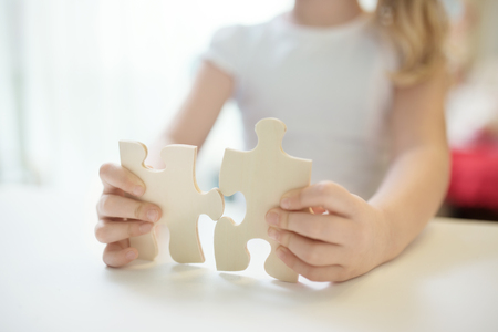 Child girl holding  two big wooden puzzle pieces. Hands connecting jigsaw puzzle. Close up photo with small dof. Education and learning concept